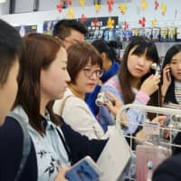 Chinese shoppers check out beauty products at a duty-free store in Tokyo's Akihabara district in 2017. | KYODO