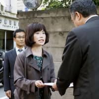 A lawyer hands over a document demanding compensation to a Tokyo Medical University official in Tokyo's Shinjuku Ward on Monday. | KYODO