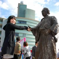 A girl shakes hands with a statue of Sakamoto Ryoma, a samurai reformist popular among history fans, in the city of Kochi, where he was born. | KYODO