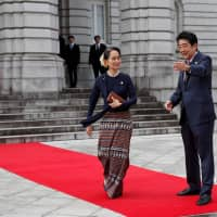 Prime Minister Shinzo Abe welcomes Myanmar's leader Aung San Suu Kyi as she arrives at the State Guesthouse in Tokyo on Tuesday for the 10th Mekong-Japan Summit. | AFP-JIJI