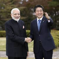 Prime Minister Shinzo Abe and his Indian counterpart, Narendra Modi, shake hands in a photo session at a luncheon Sunday at a resort hotel near Mount Fuji. | KYODO