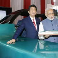 Prime Minister Shinzo Abe and his Indian counterpart, Narendra Modi, stand in front of a high-speed train simulator in Gandhinagar, in Gujarat state, during Abe's visit to India in September 2017. | KYODO
