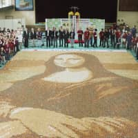 A giant Mona Lisa replica, created with 24,000 senbei rice crackers, is displayed in Soka, Saitama Prefecture, on Sunday. Guinness World Records certified it as the world's largest mosaic made of rice crackers. | KYODO