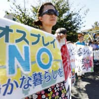 Local residents stage a protest Monday outside Yokota Air Base, a U.S. military installation, in suburban Tokyo. Five MV-22 Osprey aircraft were officially deployed at the base the same day. | KYODO