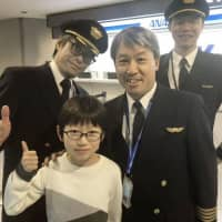 The world's youngest Othello game champion, Keisuke Fukuchi (front left), and All Nippon Airways Capt. Kunihiko Tanida (front right) pose for photos at Narita airport on Monday. | ALL NIPPON AIRWAYS CO. / VIA KYODO
