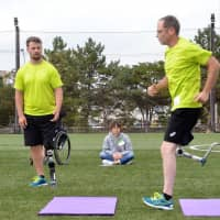 Two-time Paralympic track and field gold medalist Heinrich Popow (left) watches winter Paralympian Shawn Matheson during a running clinic event in Urayasu, Chiba Prefecture, on Sunday. | KYODO