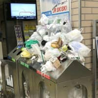 Plastic waste is piled up on a bin at a station in Tokyo. Many local governments are struggling to cope with such waste as it can no longer be exported to China. | KYODO