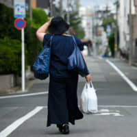 A pedestrian carries a plastic shopping bag as she walks along a road in Tokyo in August. | BLOOMBERG