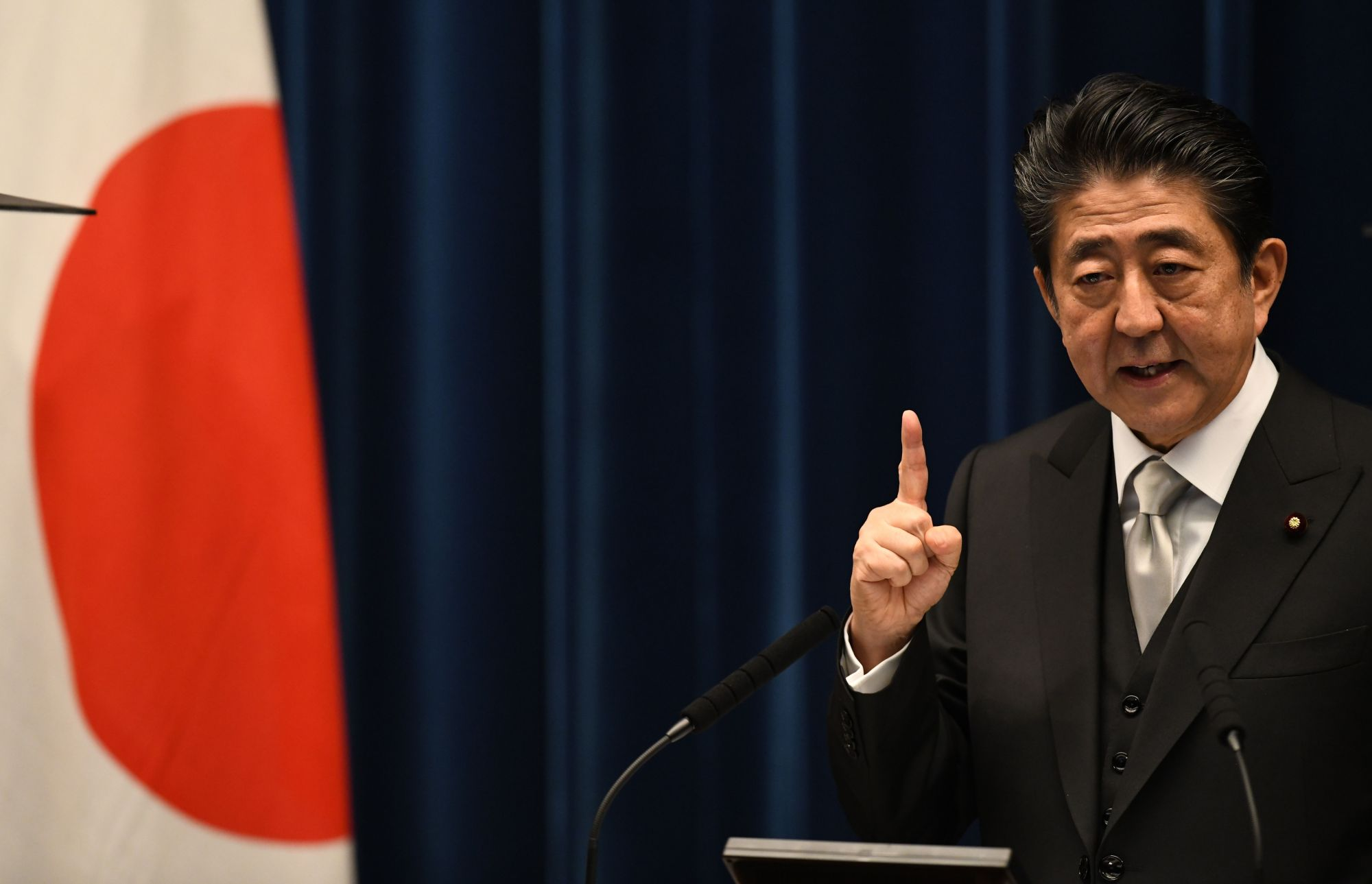 Prime Minister Shinzo Abe answers a question during a news conference after his Cabinet reshuffle Tuesday. The latest public opinion poll conducted by Kyodo News shows the approval rate for his new ministerial team is at 46.5 percent, down 0.9 points from the previous poll last month. | AFP-JIJI