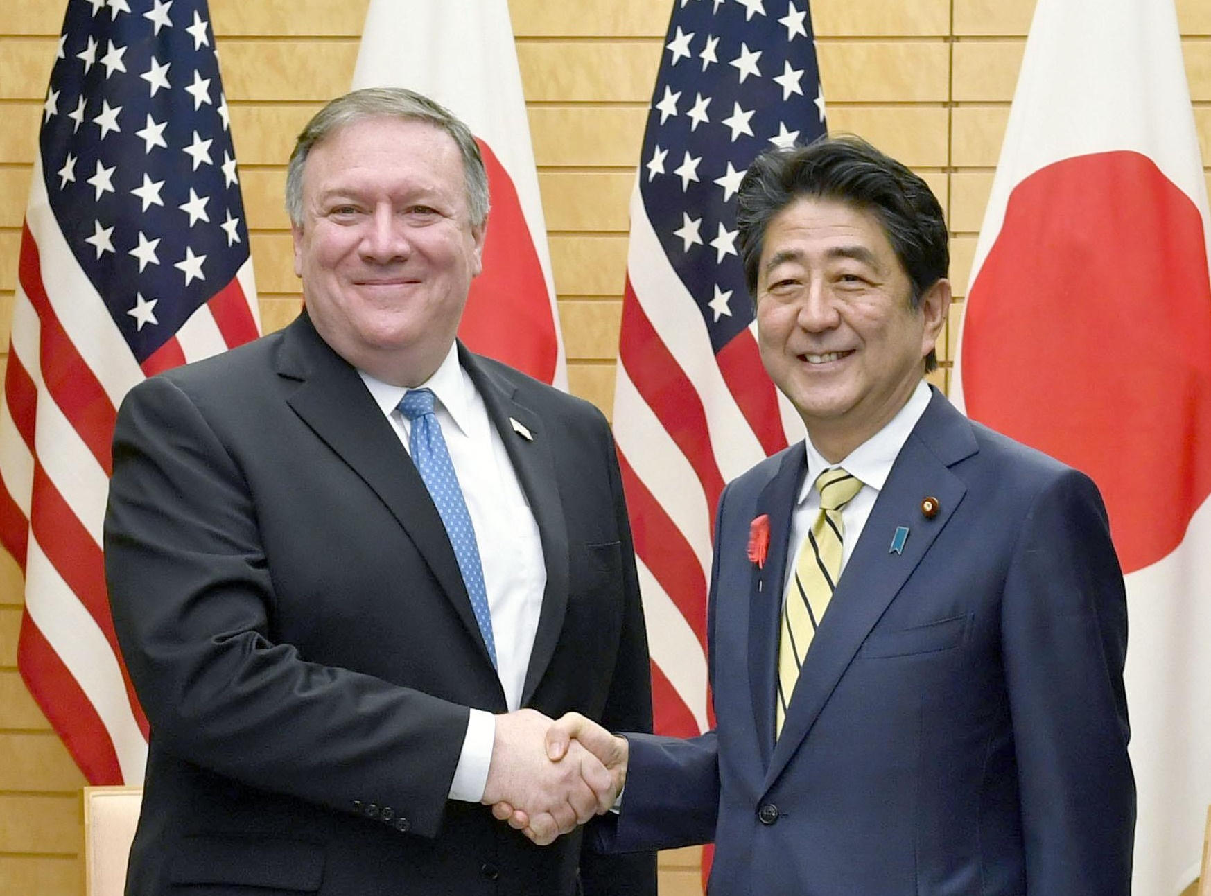 U.S. Secretary of State Mike Pompeo and Prime Minister Shinzo Abe shake hands  Saturday in Tokyo before starting a meeting to discuss North Korean nuclear and ballistic missile program issues. Pompeo will depart for Pyongyang on Sunday. | KYODO