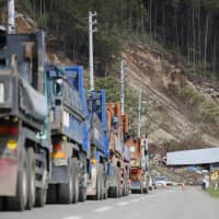 Dump trucks are parked in line Friday in the town of Atsuma, Hokkaido, after being moved from the site of a previous landslide where reconstruction work was suspended due to an earthquake in the morning. | KYODO