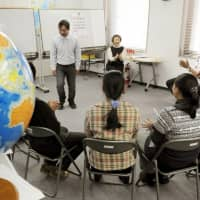 Myanmar refugees who came to Japan under the third-country resettlement program learn the Japanese language in Tokyo's Shinjuku Ward in February 2011. | KYODO