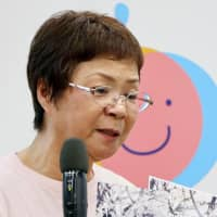 Kayo Kani, who became infected with the disease during pregnancy and is now co-head of a group working to stop rubella infections, shows photos of her daughter — who was born with heart problems and later died — in Tokyo on Thursday, where she stressed the importance of vaccinations. | KYODO