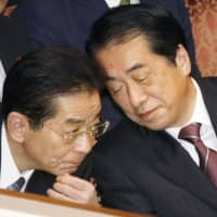 Then-Chief Cabinet Secretary Yoshito Sengoku (left) speaks to Prime Minister Naoto Kan during an Upper House session in November 2010. | KYODO