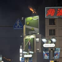 Flames are seen atop a building in Tokyo's Shibuya Ward on Wednesday as revelers gathered for massive Halloween celebrations in the area. | KYODO
