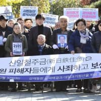 Supporters of a South Korean Supreme Court ruling that ordered a Japanese steel firm to compensate four South Koreans who were victims of forced labor during Japan's colonial rule of the Korean Peninsula gather outside the court before the decision Tuesday. | KYODO
