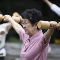 A woman exercises with wooden dumbbells during an event marking Respect for the Aged Day at a temple in the Sugamo district of Tokyo in September 2016. | BLOOMBERG