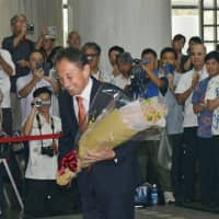 Newly elected Okinawa Gov. Denny Tamaki greets staff on his first day at the prefectural government office in Naha on Thursday. | KYODO