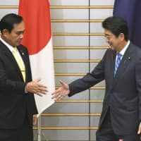 Prime Minister Shinzo Abe greets Thai Prime Minister Prayuth Chan-ocha prior to their meeting at the Prime Minister's Office in Tokyo on Monday. | AP
