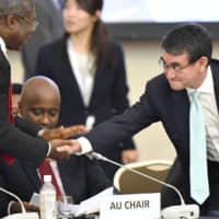 Foreign Minister Taro Kono shakes hands Sunday with one of the participants at a two-day ministerial meeting of Japan and African countries held in Tokyo. | KYODO