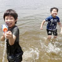 Children play with water on the beach in the Odaiba district in Tokyo's Minato Ward on June 9. A plan to filter bacteria from the water around the beach was announced Friday by the 2020 Olympic organizers. | KYODO