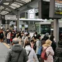 People wait in line to board city-run buses outside JR Kyoto Station in February. | KYODO