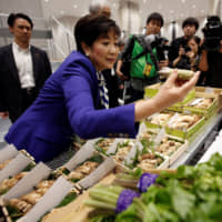Tokyo Gov. Yuriko Koike inspects wasabi at the new Toyosu fish market Thursday. | REUTERS