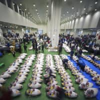 Prospective buyers bid for frozen tuna during the first auction at the newly opened Toyosu market, relocated from its former site at Tsukiji, in Tokyo on Thursday. | AP
