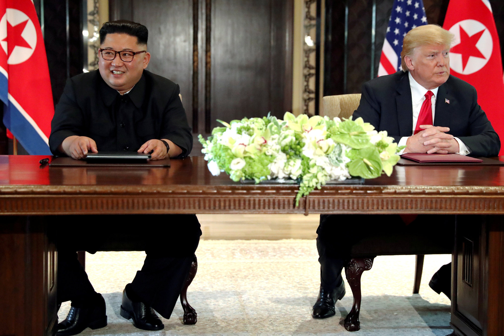 U.S. President Donald Trump and North Korea's leader Kim Jong Un hold a signing ceremony after their first meeting in Singapore on June 12. A South Korean newspaper reported Japan is ready to host a second U.S.-North Korea summit meeting.   REUTERS