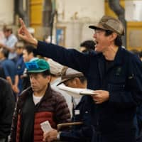 An auctioneer yells during the final tuna auction at the landmark Tsukiji fish market, the last day of the market's operations before it closes, in Tokyo on Saturday. | AFP-JIJI