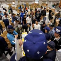 Wholesalers take part in an auction on the opening day of the new Toyosu market in Tokyo on Oct. 11. | REUTERS