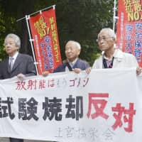 Plaintiffs hold a sign stating their opposition to the burning of radiation-tainted waste as they head to the Sendai District Court to file a lawsuit on Thursday. | KYODO