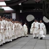 Shinto priests walk toward the main Yasukuni shrine to perform a ritual during its four-day autumn festival in Tokyo on Wednesday. | AFP-JIJI