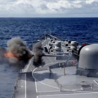 The Maritime Self-Defense Force destroyer Inazuma test-fires its 76-mm cannon in the Indian Ocean on Sept. 27. Since taking power in 2012, Prime Minister Shinzo Abe has had significant legislative successes in the security domain and now seeks to amend the Constitution to give explicit legal standing to the Self-Defense Forces. | REUTERS