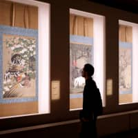 A visitor examines artworks in the 'Jakuchu: The Colorful Realm of Living Beings' exhibition. | JOHN L. TRAN