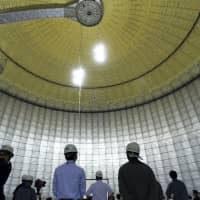 A ceremony is held inside a liquefied natural gas storage tank at Tokyo Electric Power Co.'s gas-fired thermal power plant in Futtsu, Chiba, on Sept. 10.  Japan will maintain a target for clean energy to account for 24 percent of the country's power mix by 2030. | BLOOMBERG