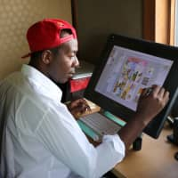 Vivid memories: Cameroon-born manga artist Rene Hoshino draws on his tablet at home in western Tokyo. | KYODO