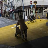 But think of the space:  An elderly woman trundles through a quiet shopping district in Kadoma, Osaka Prefecture, in June. | BLOOMBERG