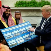 U.S. President Donald Trump holds a chart of military hardware sales as he welcomes Saudi Arabia's Crown Prince Mohammed bin Salman in the Oval Office at the White House in Washington on March 20. | REUTERS