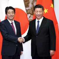 Prime Minister Shinzo Abe shakes hands with Chinese President Xi Jinping  before a meeting at the Diaoyutai State Guesthouse in Beijing on Oct. 26. | AP