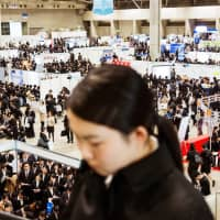 University students attend a job fair at the Makuhari Messe convention center in Chiba Prefecture in March 2017. Japanese companies need to start looking more at skills than diplomas when hiring new employees. | BLOOMBERG