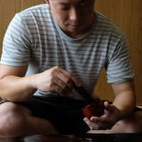 Tomoya Machida applies urushi lacquer to a cup made from mikan (tangerine)skin.   LANCE HENDERSTEIN
