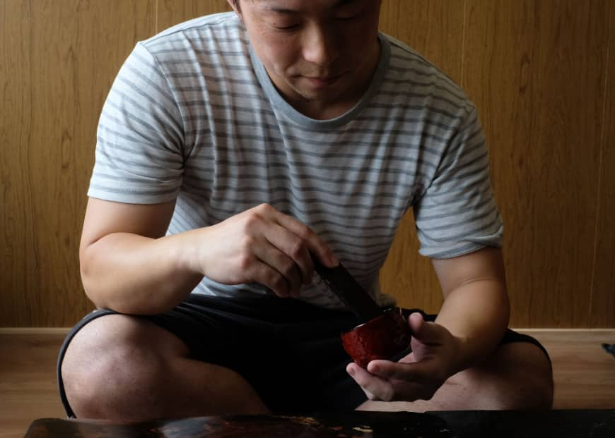 Tomoya Machida applies urushi lacquer to a cup made from mikan (tangerine)skin.