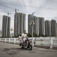 A Chinese couple ride an electric scooter in Shandong province. Asia's emerging middle class appears open to the idea of e-scooters if the price is right and charging is convenient. | BLOOMBERG