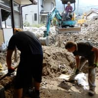 Removal men: IDRO Japan and Nippon Foundation volunteers shift sand and rocks from the porch of a home in Nakano, Hiroshima Prefecture, in late August. | SHAUN O'DWYER