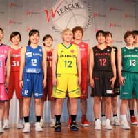 JX-Eneos Sunflowers star guard Asami Yoshida (center, in a yellow jersey) and captains of other teams pose for photos at Friday's Women's Japan Basketball League kickoff conference in Tokyo. | KAZ NAGATSUKA