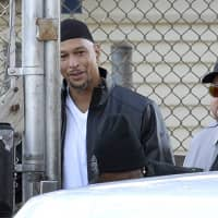 Former Carolina Panthers reeiver Rae Carruth (center rear) exits the Sampson Correctional Institution in Clinton, North Carolina on Monday. Carruth has been released from prison after serving 18 years for conspiring to murder the mother of his unborn child. | AP