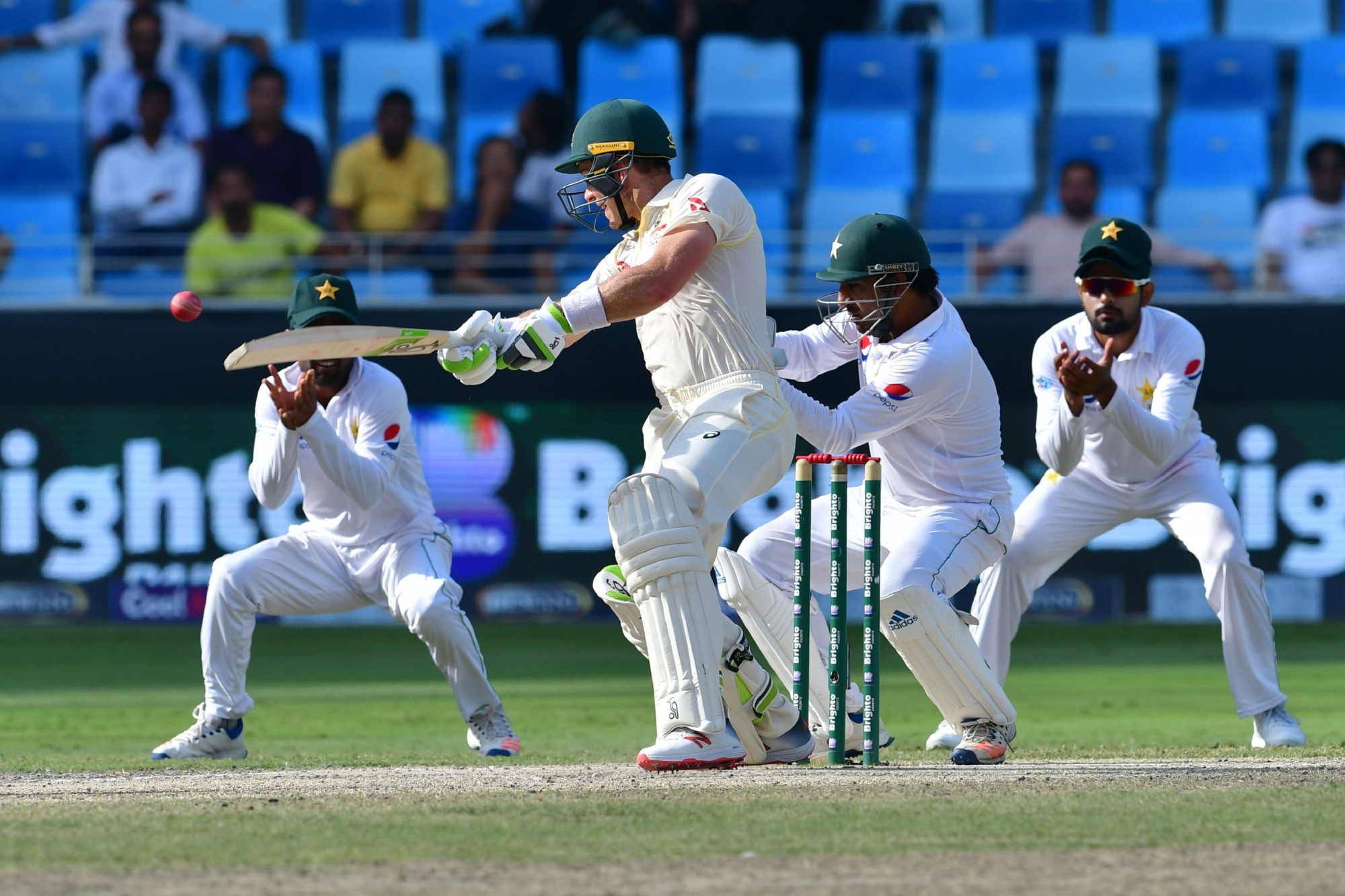 Australia's Tim Paine (center) plays a shot on the fifth day of the first test match in the series against Pakistan at Dubai International Stadium on Thursday. | AFP-JIJI