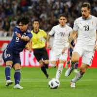 Takumi Minamino scores the opening goal for Japan against Uruguay on Tuesday in Saitama. | REUTERS