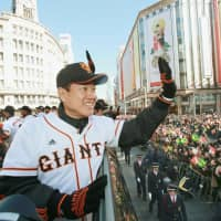Giants manager Tatsunori Hara waves to fans during a victory parade held after the club won the 2012 Central League and Japan Series titles. | KYODO